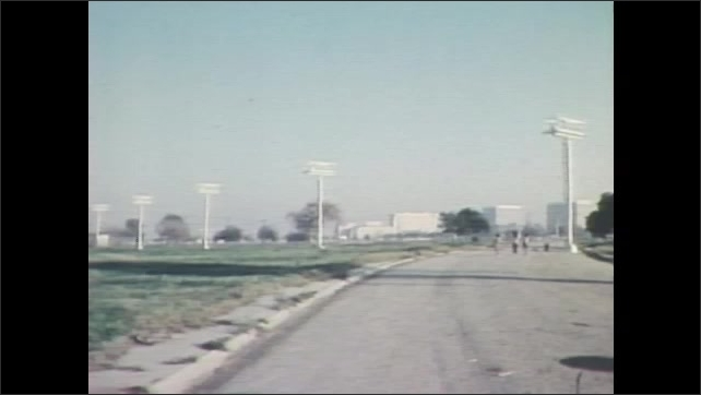 "1980s: Palm tree. Kids walk down an empty street, then begin running. A street sign reads ""Kittyhawk Ave. 9000 S."""