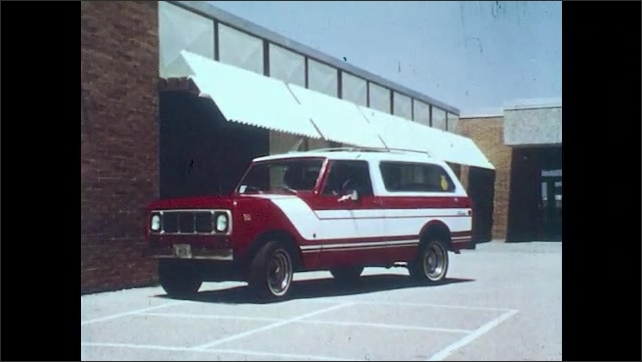 1970s: Truck pulls up to building. Man and boys exit truck.