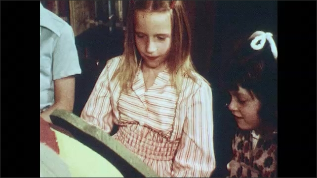 1970s: Hands put tomatoes in basket. Boy with large model of pickle. Girls look at pickle model. Cucumbers pour into bin. People sort cucumbers. Pickles on conveyor belt.