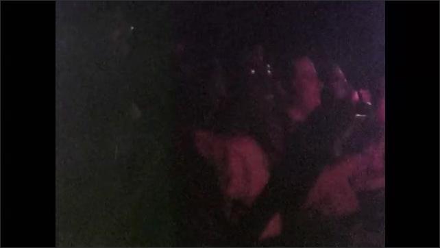 1970s: Girl uses spinning wheel.  Audience claps in dark room.