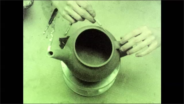 1970s: Woman works on clay teapot.