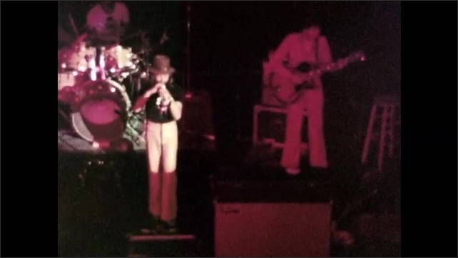 1970s: Band plays on stage.