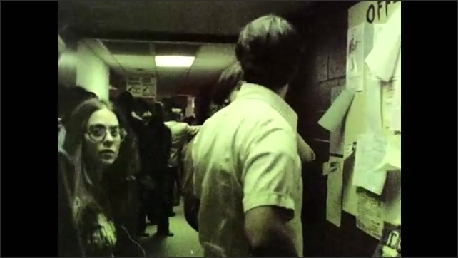 1970s: Man plays guitar and sings.  Crowded hallway.  College students wait in line.