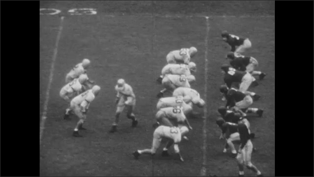 1940s: Football game.  Man catches ball.  Spectators.  Man runs.  Man is tackled.