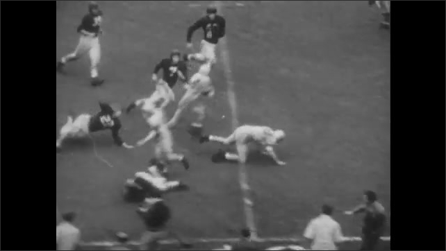 1940s: Football game.  Player runs with ball.  Man pushes player.  Men fall.