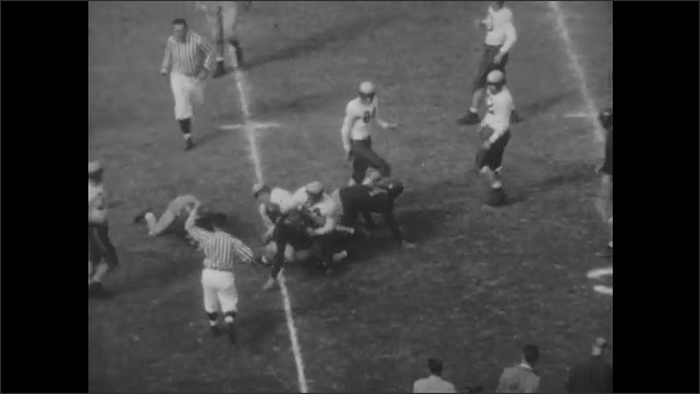 1940s: Football game.  Spectators.  Players throw ball and run.  Men tackle players.