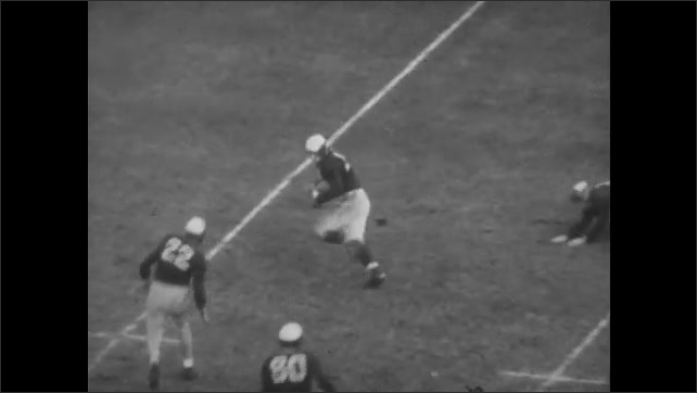 1940s: Football game.  Fans stand.  Player grabs ball off ground.  Player is tackled.  Fans pull down goal post.  Men fight.