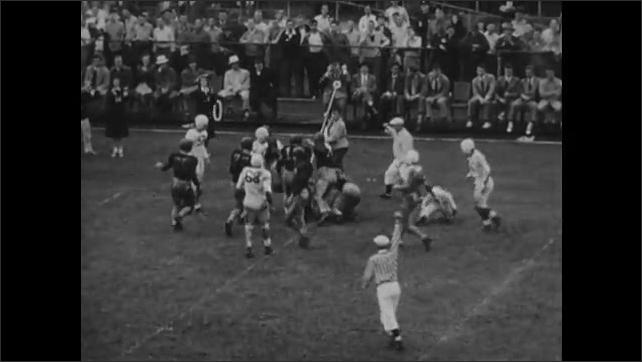 1940s: crowds of fans in stadium cheering, quarterback throws interception, running back scores touchdown