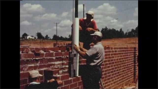 1950s: Men look at blueprint on construction site.  Men work on pipe.  Welder.  Men lay bricks.