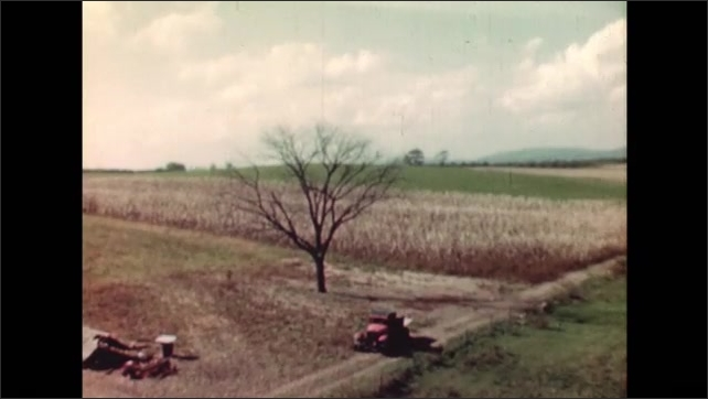 UNITED STATES 1940s: person opens door and closes it / view of crops / horse and tractor harvesting crops