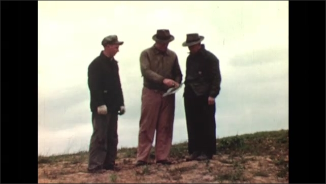 UNITED STATES 1940s: man pulling branches / man hitting tree with hammer / 3 men staring at a paper on a field / man doing hand movements to 2 other men
