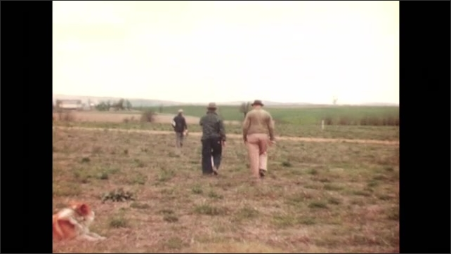 UNITED STATES 1940s: close up of screw in wood / 3 men walk further into field, then stop / man raises hand and man moved directly in front of him