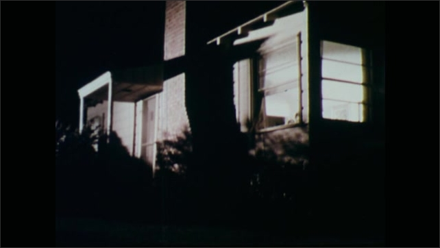 1970s: Policemen walk across yard at night, hold guns. Police crouch by door of house. Police kick in door of house.