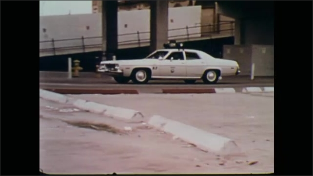 1970s: Police car drives out of lot, drives down street.