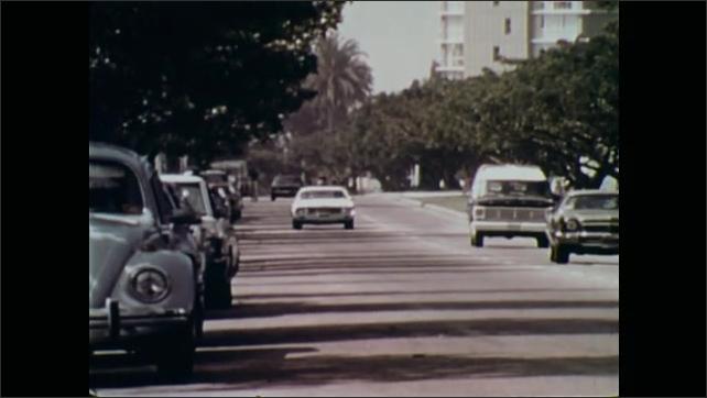 1970s: Cars drive down street.