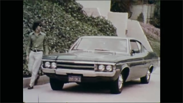 1970s: Man looks under hood of car, looks away. Car drives up street, parks in front of house. Men exit car, walk across street, enter house.