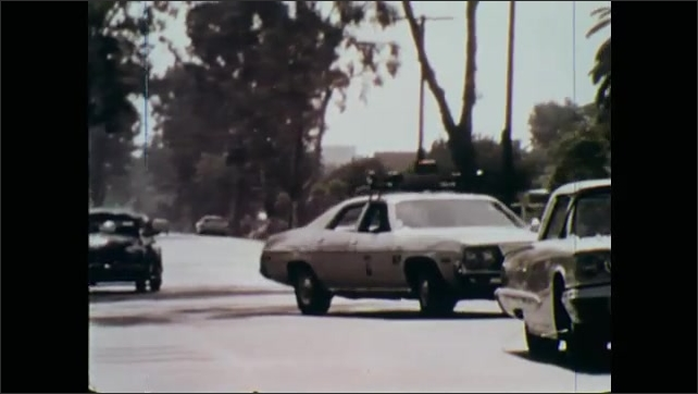 1970s: Patrol car drives down street.