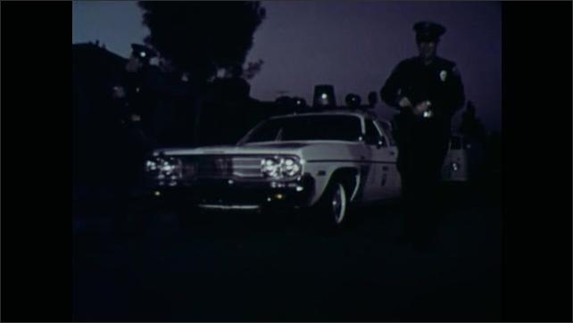1970s: Policemen exit patrol car, policeman carries gun. Policemen talk, walk across street.