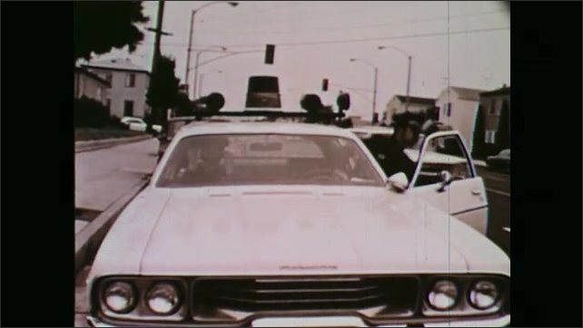 1970s: Police car pulls up to sidewalk, officers exit, walk to man outside of house.