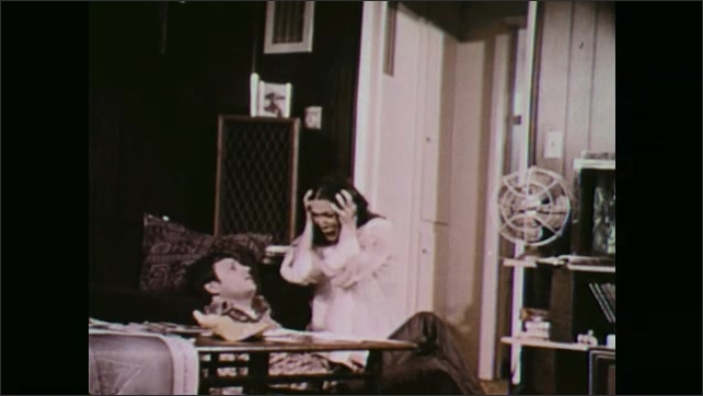 1970s: Man and woman in living room. Police officer fires gun. Man falls, woman drops to knees. Close up of officer.