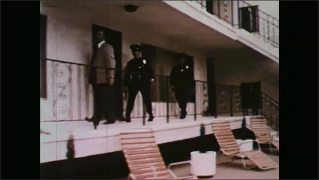 1970s: Women talking by table, man enters with beer. Woman talking. Man and women by table. Tracking shot, police officers walking through apartment complex, woman exits door.