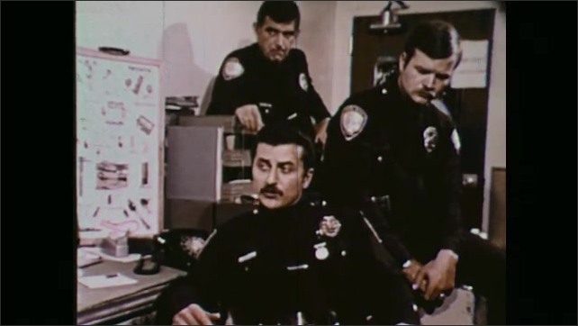 1970s: Police officers in room, officer hangs up phone, zoom in on officer talking.