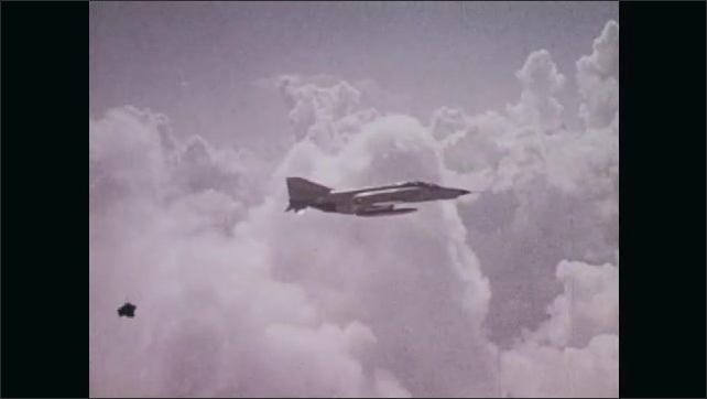1970s: View through cockpit, Rough Rider Air Force jet flies through clouds. Air traffic control office, man watches radar screen, turns knobs, man wears headphones, holds clipboard and radio.