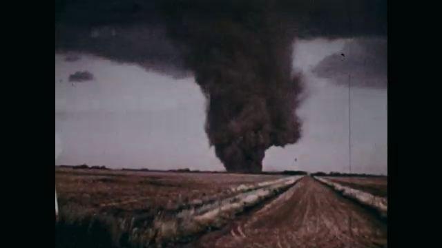 1970s: Dirt road, expansive agricultural field, tornado, huge plume of black smoke rising, swirling.