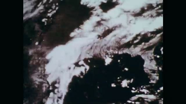 1970s: Satellite image of clouds swirling. Small jet, man reads, man taps pilot on shoulder, talks. Clouds over fields.