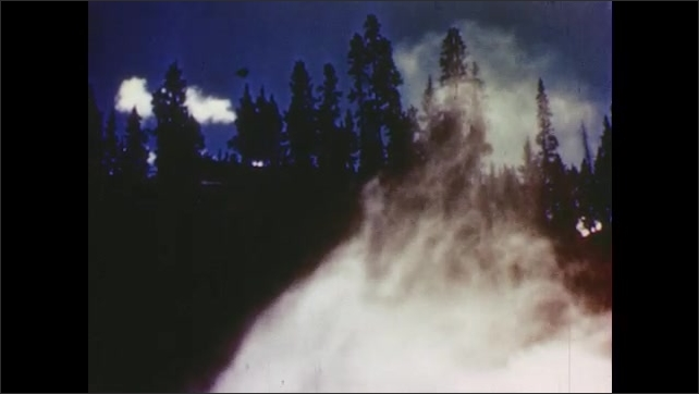 1950s:  white smoke or clouds flow through a mountain passage with pine trees on the peaks.