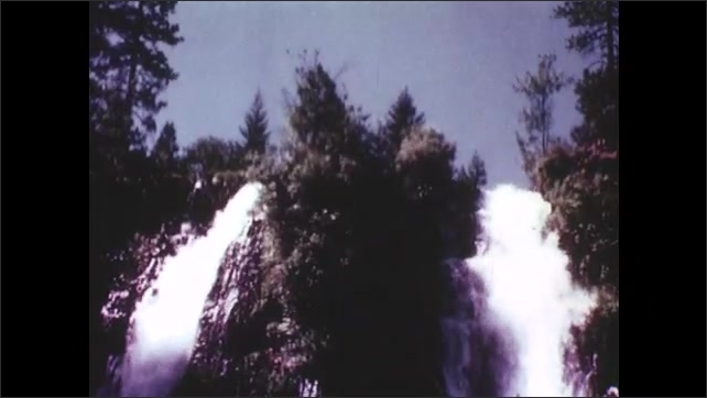 1950s: Grassy field in front of snow covered forest. Waterfalls flow down cliffs.