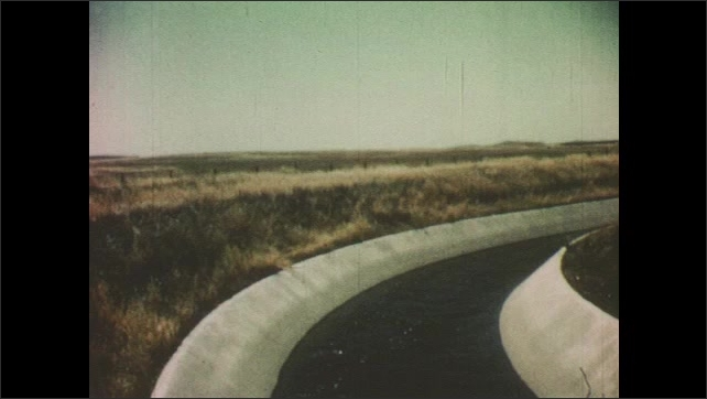 1950s: Water runs in tree-lined stream. Water runs in cement irrigation channel. Irrigation channel runs through growing fields.