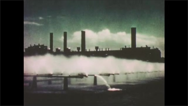 1950s: Electrical towers. Plant with exhaust next to river. Aerial view of city.