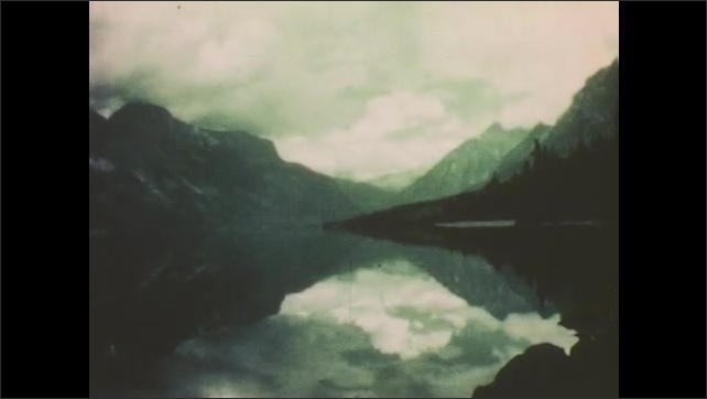 1950s: Mountain peaks. Mountains and clouds reflected in lake. Deer at foot of large tree.