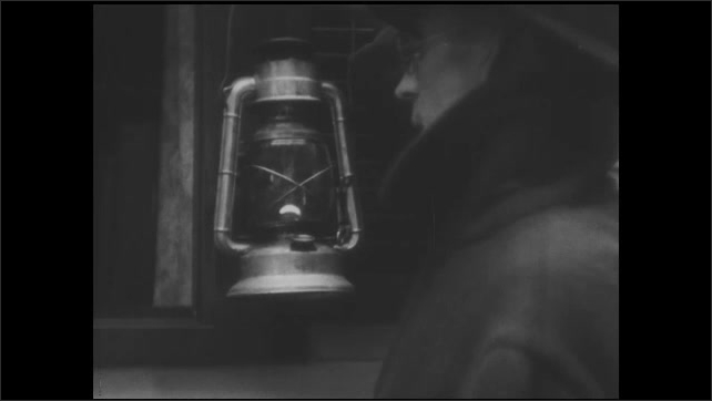 1930s: House in woods. Man approaches window of house holding lantern. Title card. Man stands outside window talking to woman inside. Woman inside window. Title card. Man holds lantern. Title card.