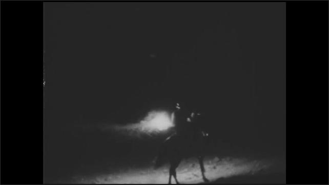 1930s: UNITED STATES: nurse rides horse through woods at night. Nurse carries lamp.