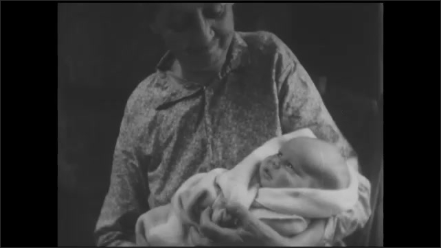 1930s: Title card. Woman sits holding baby in front of fire. Woman sits holding baby. Midwife picks up baby from woman. Midwife holds and talks to baby.