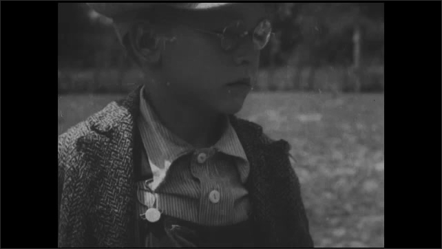 1930s: UNITED STATES: close up of boy with glasses. District nurse speaks to children. Girl looks at nurse. Close up of boy with freckles