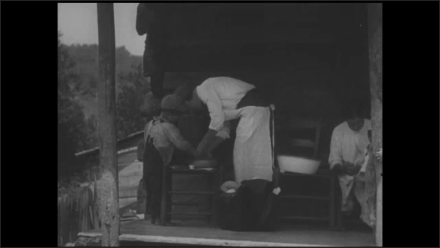 1930s: UNITED STATES: district nurse tends to small boy's hand. Lady and small boy on porch