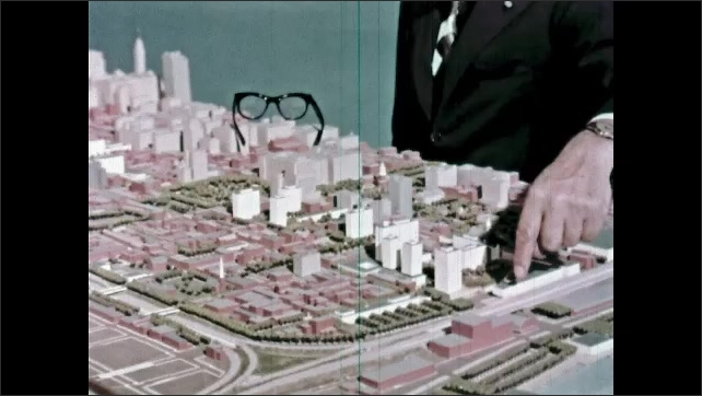 1960s: Hand pointing to features on model city. Man talking by model city.