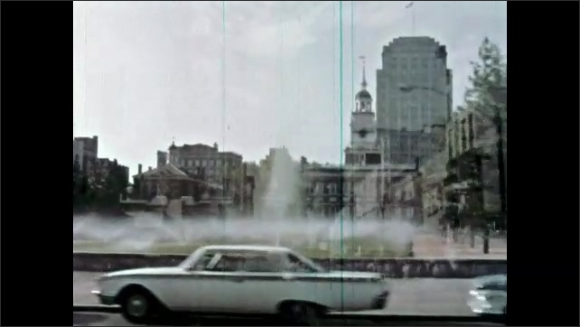 1960s: Tracking shot, driving past city square. Driving through city.