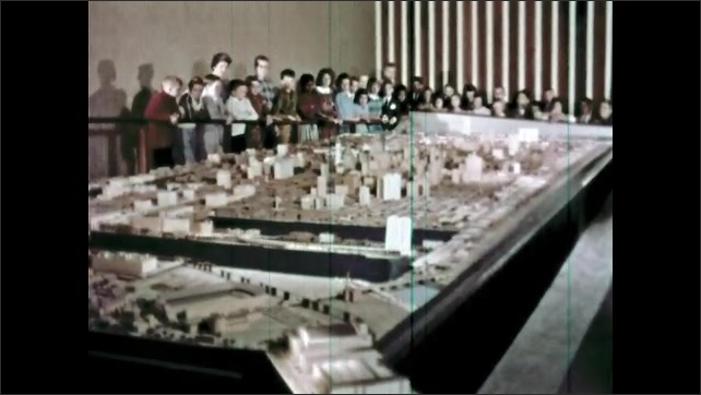 1960s: Crowd around model of city, portion of model rotating. View over shoulder, man watches swinging magnifying glass.