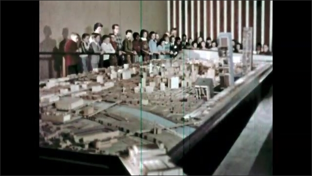 1960s: Man talking by scale model in front of class. Crowd around model of city, pieces of model moving.