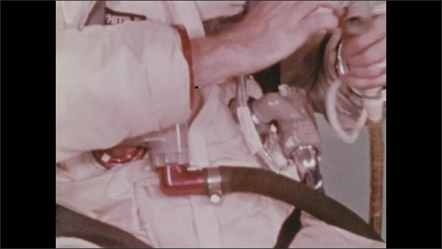 1960s: Man connects tubes on space suit.