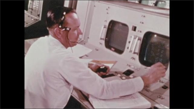 1960s: Mission control room.  Man speaks into headset.