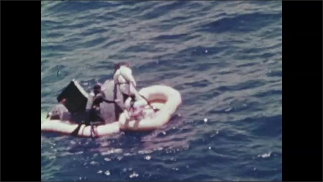 1960s: Helicopters flying above ocean. Diver jumps from helicopter to ocean. Diver assists astronaut from spacecraft in water to inflatable raft. They are raised from raft into helicopter.