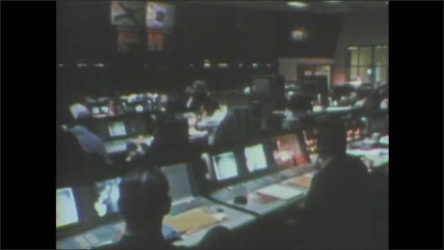1970s: Mariner 9 space probe. People sit and work in mission control at NASA. Mariner 9 space probe rotates.