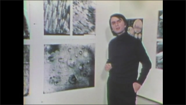 1970s: Carl Sagan talks and points to photographs of the surface of Mars that hang on the wall.