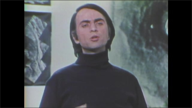 1970s: Carl Sagan talks and gesticulates with posters behind him.