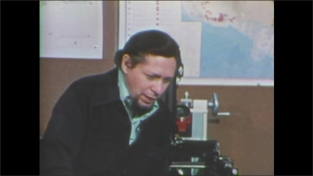 1970s: Face of Carl Sagan who talks to the camera. Man sits and talks, stands up, talks and gesticulates, maps hang on the wall in background.